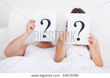 Couple Lying On Bed Holding Question Mark