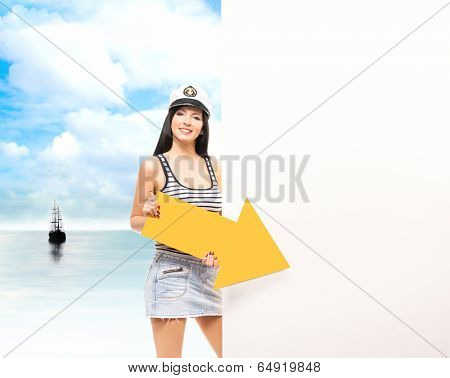 Young, beautiful and sexy sailor girl over sea and sky background
