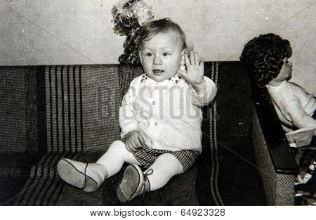 LENINGRAD (now St. Petersburg), RUSSIA - CIRCA 1970-th: Antique photo shows portrait of a little girl sitting on the sofa .