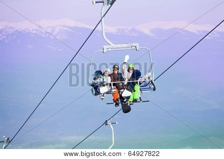 Three snowboarders sit on ropeway in mountains