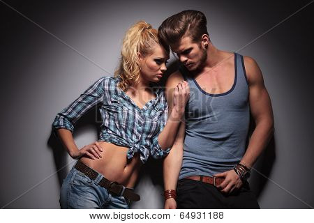 passionate couple standing against gray studio wall, in a hot pose