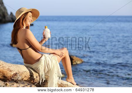Woman On Holidays  On The Beach Applying Sunscreen Protection On Leg