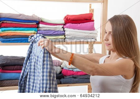 Young caucasian woman standing near the wardrobe and holding clothes