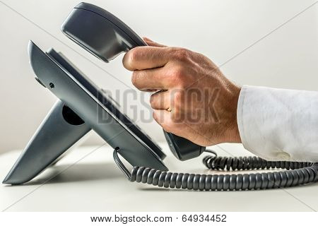 Male Hand Picking Up The Receiver Of A Telephone