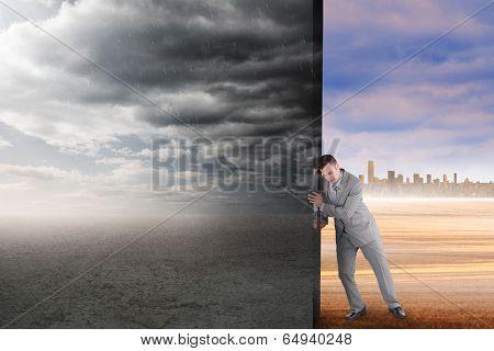 Composite image of businessman pushing away scene of ominous landscape