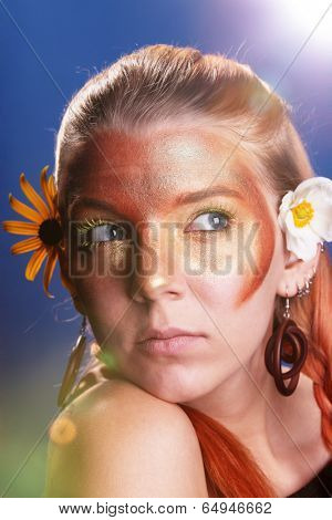 Girl with atractive make-up and a flower in her hair.