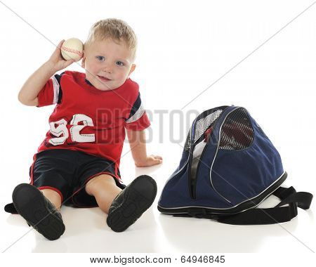 A young preschooler ready to toss the baseball he's just pulled from his sports bag.  On a white background.