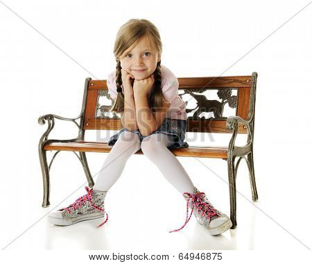 An adorable young elementary girl sitting on a park bench with sparkly, oversized, high-top sneakers tied with neon pink laces covered with hearts.  On a white background.