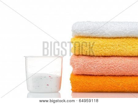 Detergent for washing machine in laundry with towels in the white background.