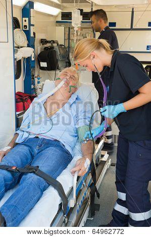 Paramedical team examining injured senior patient lying on stretcher
