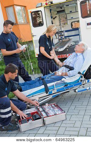 Paramedic team assisting injured senior man lying on stretcher outdoors