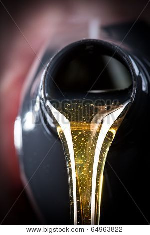 Motor oil pouring over black background