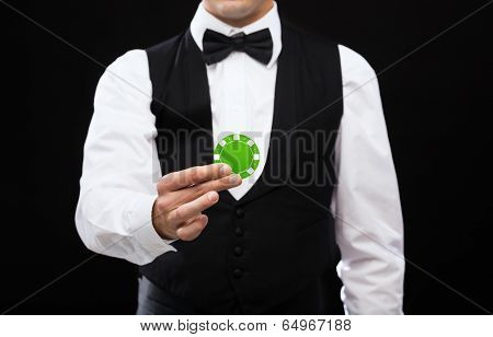 magic, performance, circus, casino and show concept - casino dealer holding green poker chip