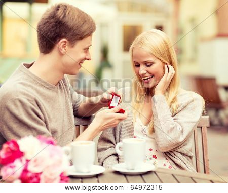summer holidays, love, travel, tourism, relationship and dating concept - romantic man proposing to beautiful woman