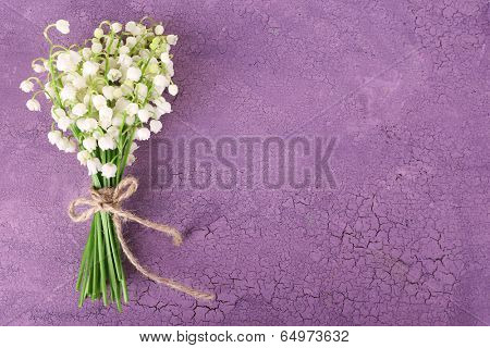 Beautiful lilies of the valley on old wooden background