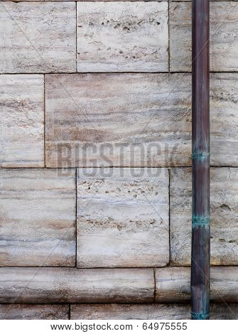 Stone wall and old copper downspout background texture