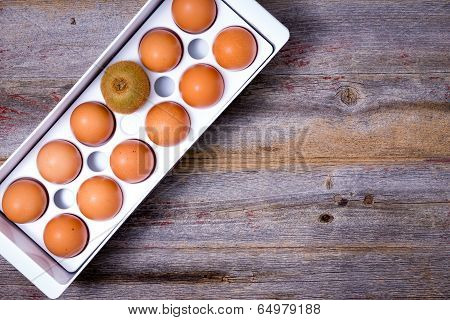 One Different Kiwifruit In A Tray Of Eggs