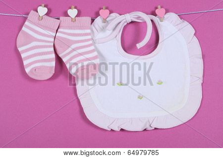 Baby Girl Nursery Cute Pink And White Stripe Socks And Bib Hanging From Pegs On A Line