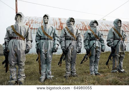 A Group Of Soldiers With Guns In Their Masks And Protective Clothing.
