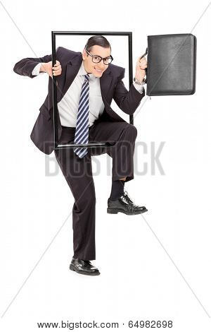Businessman walking through a frame isolated on white background
