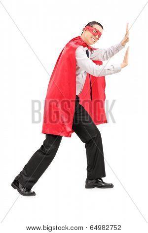 Male superhero mimicking that he is pushing something isolated on white background