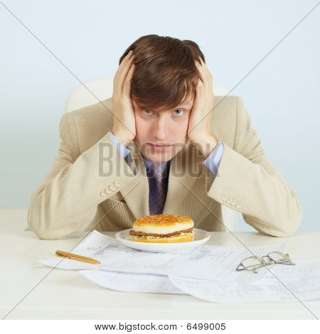 Person At Office On Workplace With A Hamburger