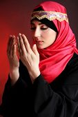 stock photo of burka  - Beautiful muslim arabic woman praying on dark color background - JPG