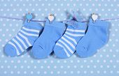pic of teething baby  - Baby boy nursery blue socks and butterfly hanging from pegs on a line against a blue polka dot background for baby shower or newborn greeting card - JPG