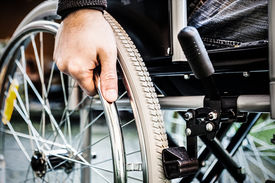 stock photo of wheelchair  - Paralyzed man using his wheelchair - JPG
