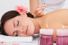 foto of stimulating  - Young Woman Lying On Massage Table Getting Acupuncture Therapy From Masseuse - JPG