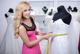 foto of dress mannequin  - Designer wedding dresses measures the dress on a mannequin in her shop - JPG