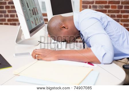 Young businessman resting head on computer keyboard in the office
