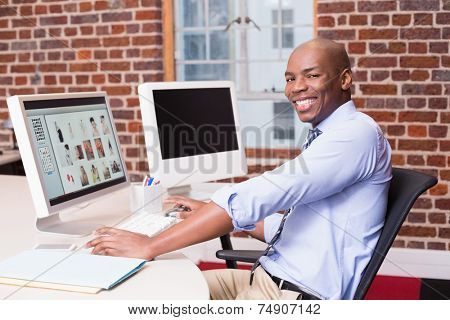 Portrait of smiling male photo editor using computer in the office