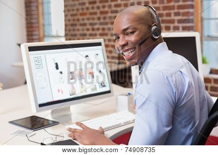 Happy young businessman using computer in the office