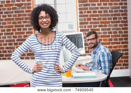 Portrait of smiling young businesswoman with hands on hips in office