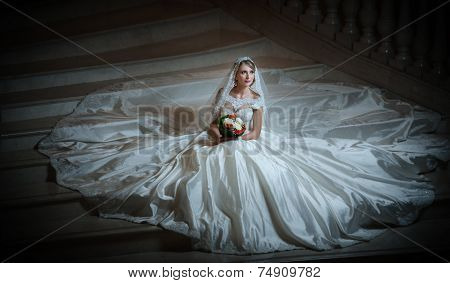 Young beautiful luxurious woman in wedding dress sitting on stair steps in semi-darkness. Bride