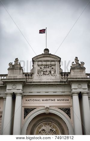 Entrance to the National Maritime Museum with its carved stone facade, arch, pillars and coat of arms below the Union Jack flag, the national ensign of Great Britain