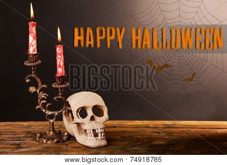 Bloody candles for Halloween holiday and decorative skull on pumpkin, on wooden table, on dark background