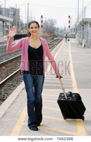 mujer ondeando en la estación de tren