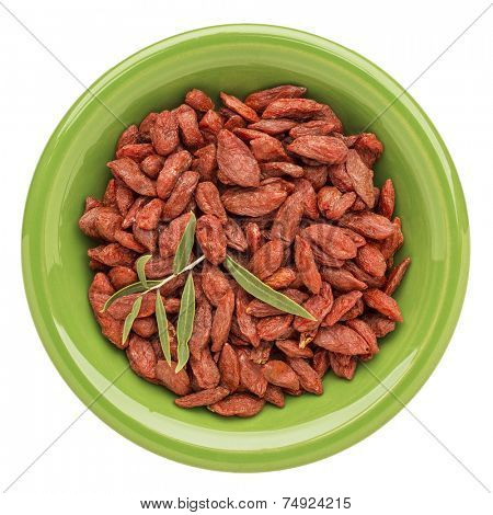 dried goji berries with a fresh leaf on an isolated green ceramic bowl