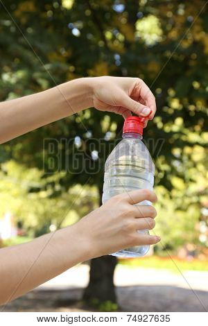 Hand opening bottle with water on bright background