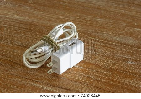 White Smartphone Charger On Wooden Background
