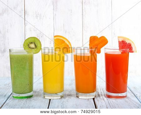 Fruit and vegetable juice in glasses and pieces of fresh fruits on wooden table on wooden wall background