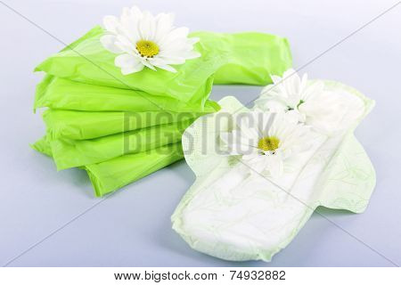 Sanitary pads and white flowers on light background