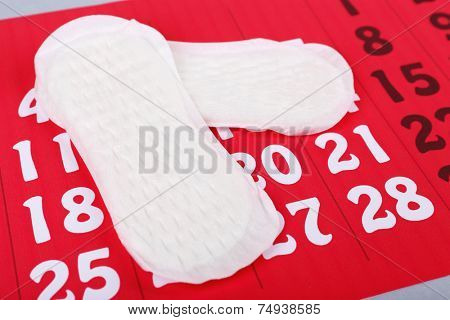Sanitary pads on red calendar background