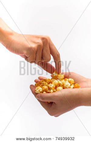 Hand Picking Caramel Popcorn Filled Another Hand