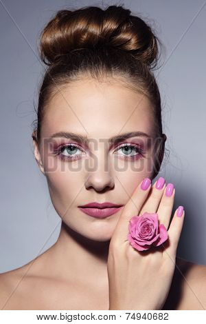 Young beautiful girl with stylish pink manicure and hair bun