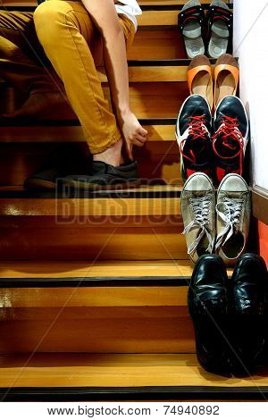 Person sitting and putting on shoes beside Different shoes on a staircase