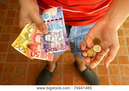 Person holding money and coins in his hand