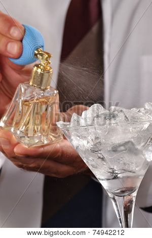 Barman preparing alcoholic cocktail drink and.spraying scent on ice glass.